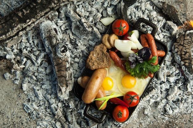 Копченые колбаски с помидорами и яйцом лежат на углях. блюдо готовят и коптят на углях