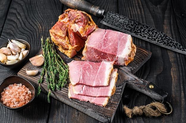 Копченая нарезанная свиная корейка мясо на деревянной разделочной доске