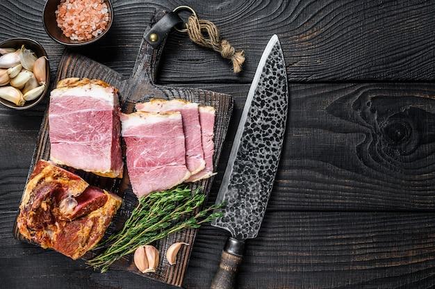 木製のまな板にスライスした豚ロース肉の燻製