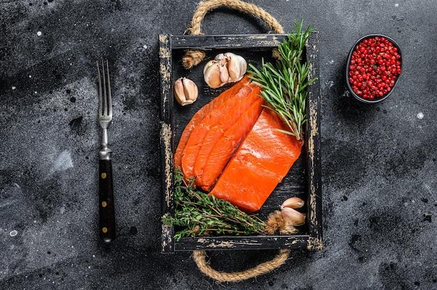 Копченое нарезанное филе лосося на деревянном подносе с зеленью. черный фон. вид сверху.
