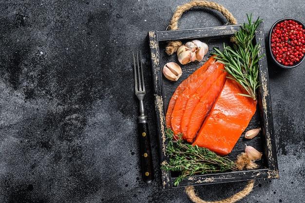Копченое нарезанное филе лосося в деревянном подносе с зеленью на деревянном столе. вид сверху.