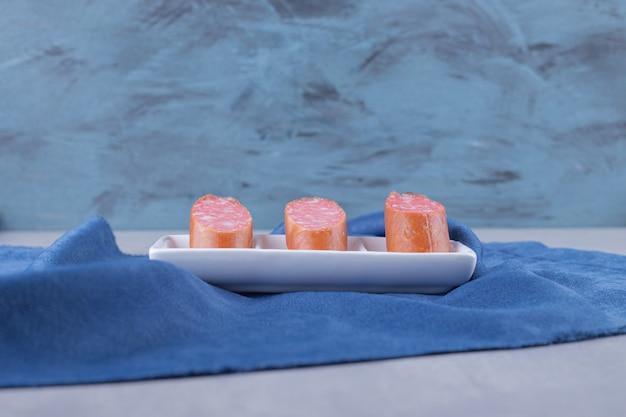 하얀 접시에 슬라이스 소시지를 훈제.