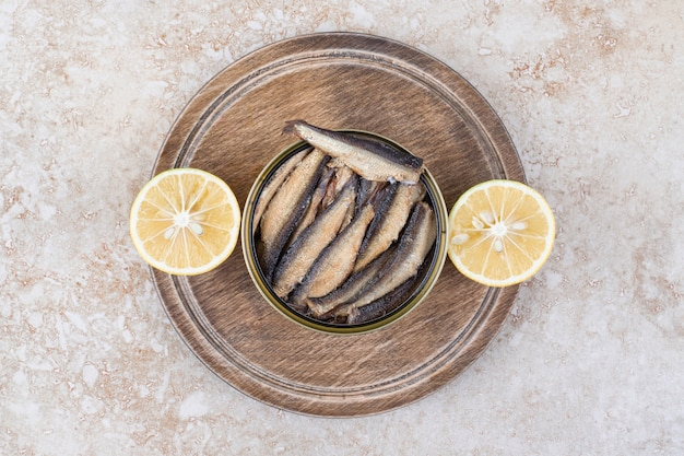 Pesce piccolo affumicato in ciotola con fette di limone