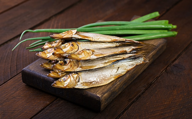 Smoked sprat and green onion  on a cutting board