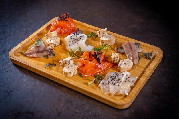 Копченый стол на черном фоне, морепродукты, разнообразие рыбы и морепродуктов