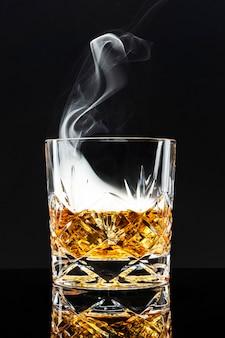 Cocktail di whisky affumicato su sfondo nero
