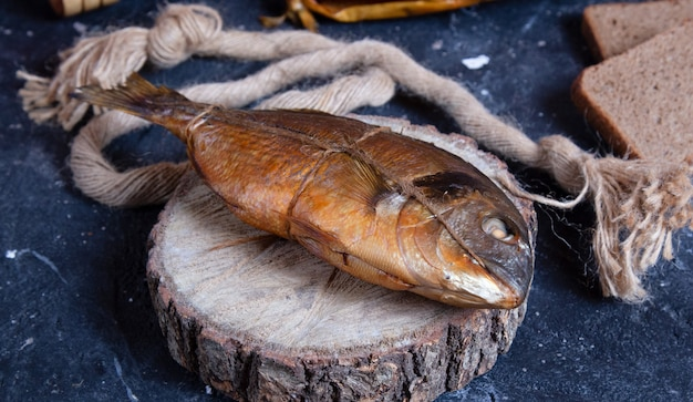 Smoked whole dry fish on a piece of wood. rustic thread around