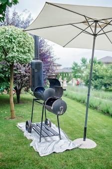 야외 녹색 정원 배경에서 집 뒤뜰 가족 파티오 야외 바베큐 파티에서 흡연자 그릴