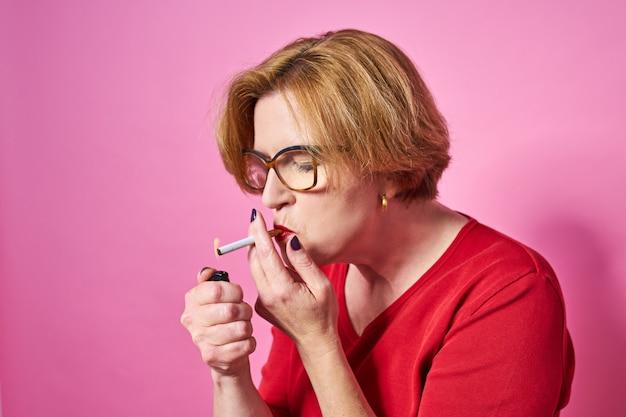 Курильщик портрет пожилой женщины курит сигарету.