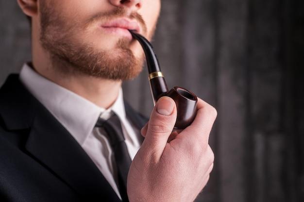 パイプを吸う。パイプを吸って目をそらしている正装でハンサムな若いひげの男のトリミングされた画像