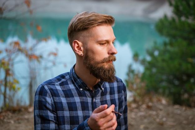 Smoking bearded man outdoors near lake in the evening bad habit addiction to cigarettes caucasian gu...