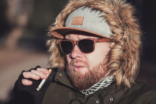 Smoking bearded man with a cigarette in a winter fur jacket