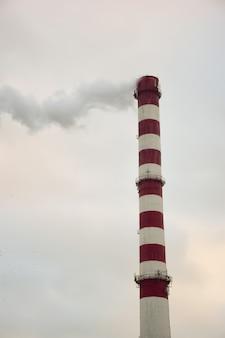 하늘을 배경으로 공장이나 공장의 굴뚝을 피우다