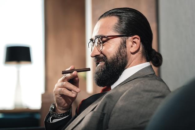 葉巻を吸う。長い疲れた交渉の後、葉巻を吸っている間、冷えている眼鏡をかけているひげを生やしたビジネスマン
