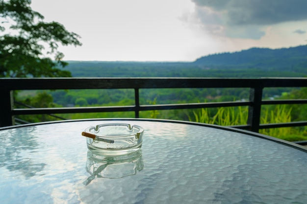 Smoking cigarette in ashtray on the glass table.