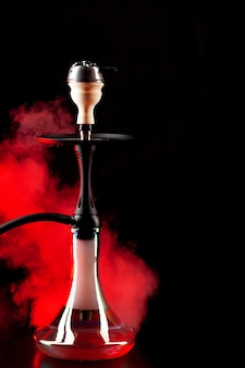 Smoking hookah on black background with color fog copy space