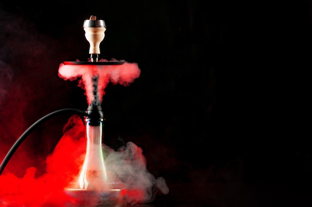 Smoking hookah on black background