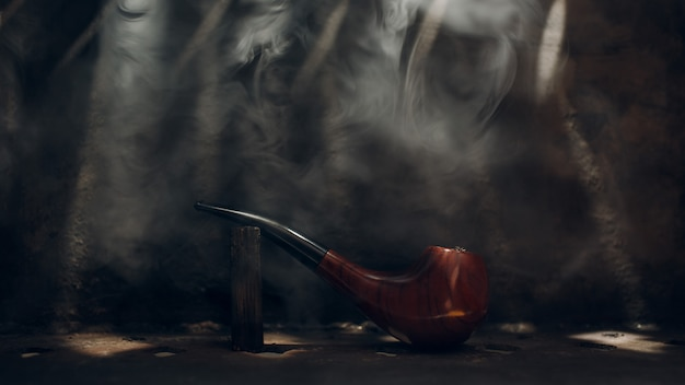 鋼の背景にタバコの煙と光線とパイプ桜材を喫煙