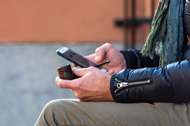 Smoking pipe and smartphone in male hands, close-up