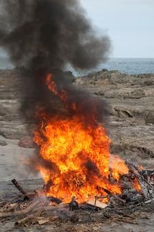 ビーチで激しく煙を燃やす赤い焚き火