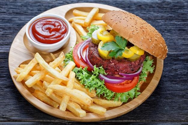 피클 신선한 양상추, 토마토, 상단에 참깨, 감자 튀김, 소박한 어두운 나무 테이블에 대나무 접시에 케첩, 근접 롤빵 안에 붉은 양파와 연기가 자욱한 비트 버거