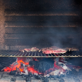Smoky grilled meat on baked metal sheet in the barbecue