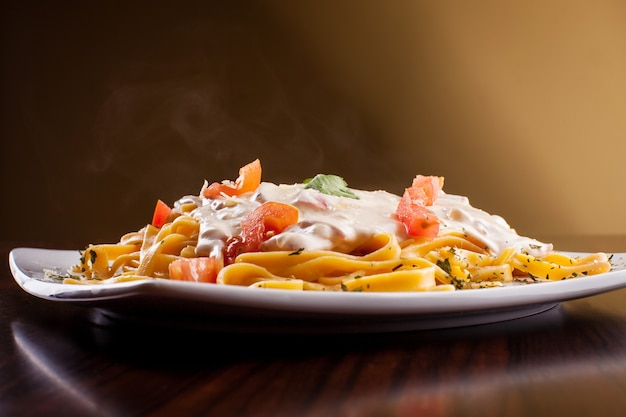 Smoky pasta with tomatoes and white sauce on wooden background