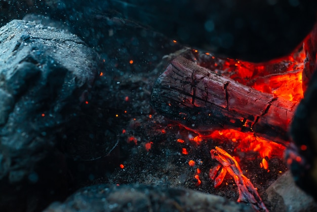 Smoldered logs burned in vivid fire close up. atmospheric background with orange flame of campfire. unimaginable detailed image of bonfire from inside with copy space. smoke and glowing embers in air.
