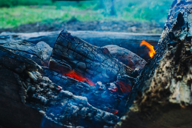 Smoldered logs burned in vivid fire close up. atmospheric background with orange flame of campfire. unimaginable detailed image of bonfire from inside with copyspace. smoke and glowing embers in air.