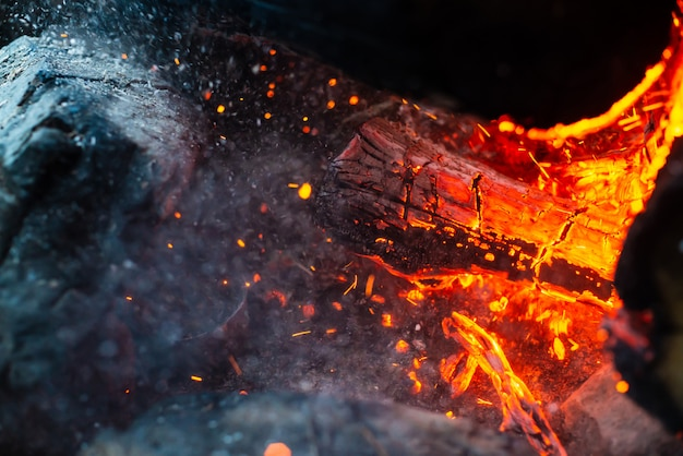 Smoldered logs burned in vivid fire close up. atmospheric  with flame of campfire. unimaginable detailed image of bonfire from inside with copyspace. whirlwind of smoke and glowing embers.
