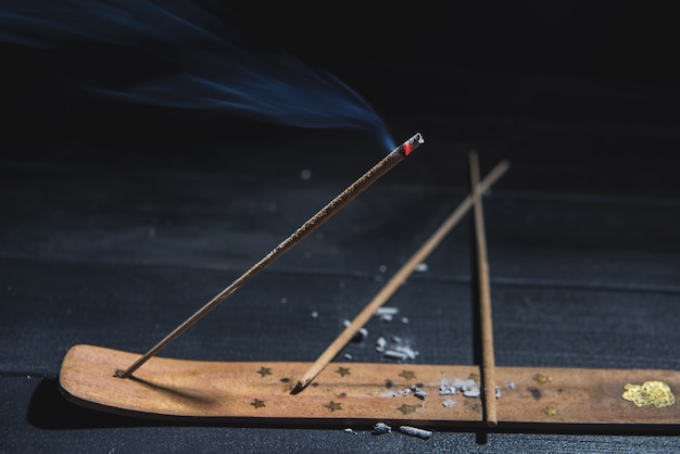 Smoldering aromatic stick in the dark with a lot of smoke for yoga meditation