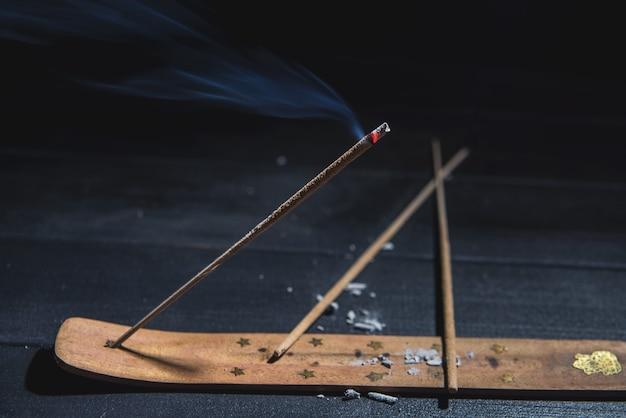 Тлеющая ароматическая палочка в темноте с большим количеством дыма для медитации йоги