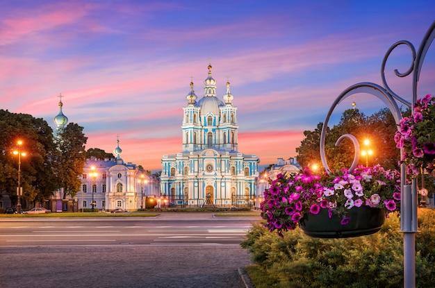 Смольный собор в санкт-петербурге на фоне заходящего розового неба и ярких цветов петунии