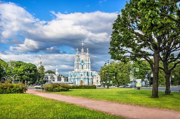 Смольный собор в санкт-петербурге в летний солнечный день и зеленые деревья и трава