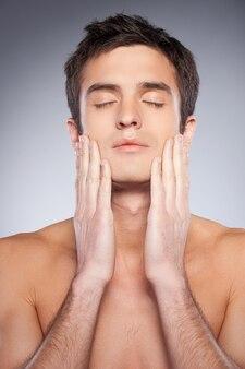 Гладкая и здоровая кожа. красивый молодой человек без рубашки, касаясь его лица руками и с закрытыми глазами, стоя на сером фоне
