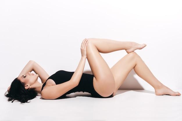 매끄럽고 빛나는 다리. 흰색 배경 앞에 누워있는 동안 그녀의 완벽한 다리를 보여주는 검은 수영복에 매력적인 젊은 여자의 측면보기