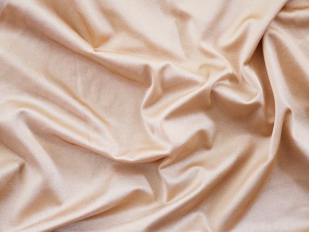 Гладкая бежевая шелковая или атласная текстура роскоши для свадебного фона.