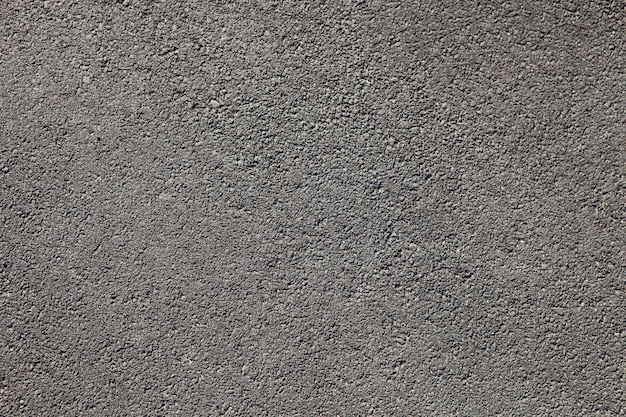 Smooth dark grey asphalt pavement texture background with small rocks