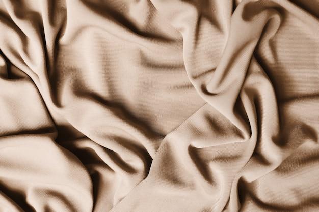 Гладкую элегантную бежевую атласную текстуру можно использовать в качестве абстрактного фона. роскошный дизайн фона. текстура крупным планом