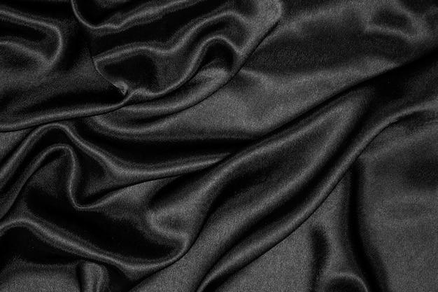 滑らかでエレガントな黒のシルクまたはサテンの豪華な布の質感