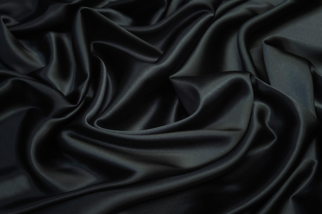 Smooth elegant black silk satin fabric texture  as abstract background. luxurious pattern for design.
