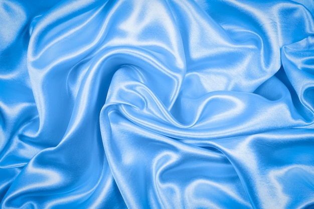 Smooth elegant blue silk or satin texture can use as abstract background. fabric color