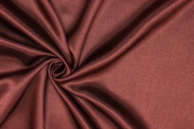 滑らかでエレガントな茶色のシルクまたはサテンの豪華な布の質感