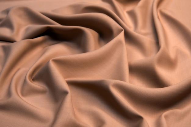 Гладкая элегантная текстурированная ткань шелкового атласа коричневого цвета для использования в качестве абстрактного дизайна.
