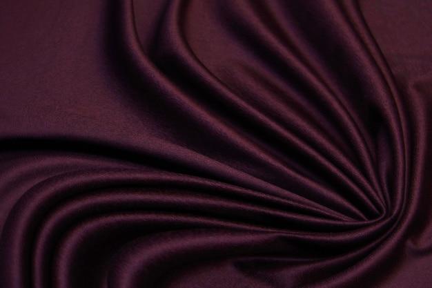 Гладкий элегантный бордовый розовый шелк или атласная ткань текстуры фона для дизайна