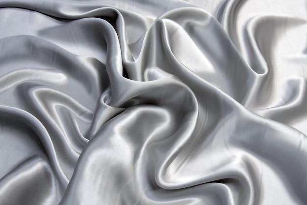 滑らかでエレガントなダークグレーのシルクまたはサテンの質感の背景。デザインのための豪華なパターン