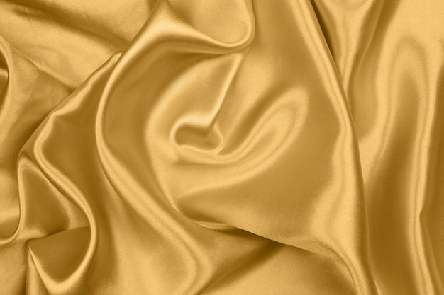 Smooth elegant gold silk or satin texture can use as abstract background