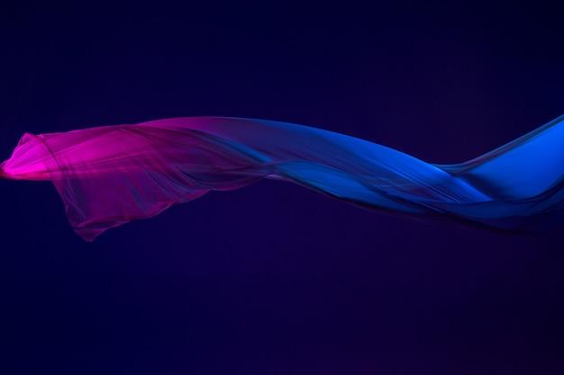 青の背景に区切られた滑らかなエレガントな透明な青い布。