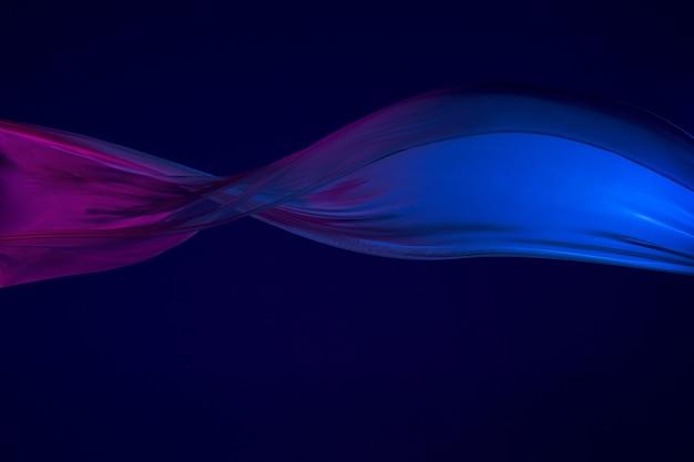 Гладкая элегантная прозрачная синяя ткань разделена на синем фоне.