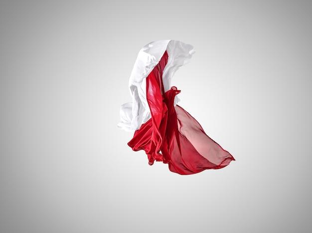 Гладкая элегантная прозрачная красная и белая ткань разделены на сером фоне.